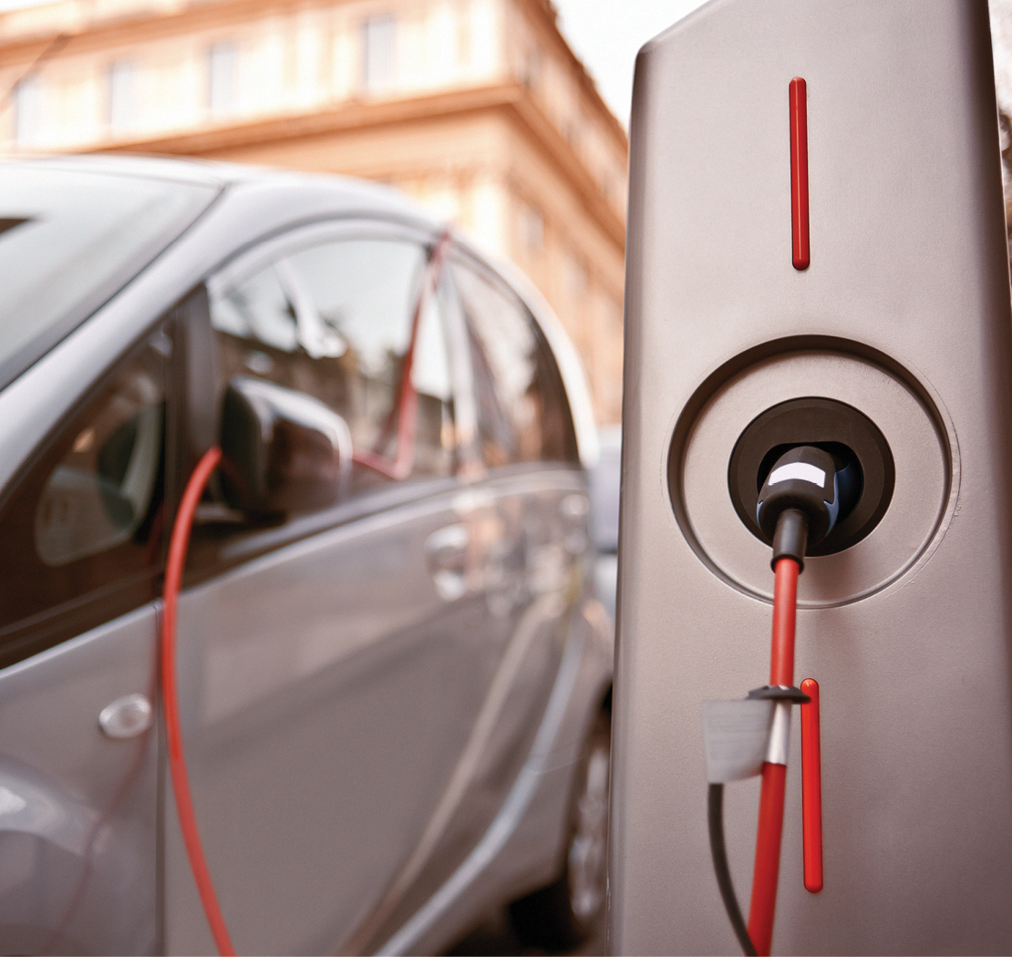 Photograph of a car using an electric charging station.