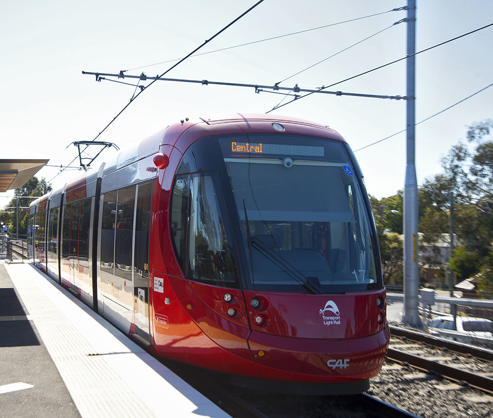 Photograph of a light rail tram heading headed towards Central stopped at a station.
