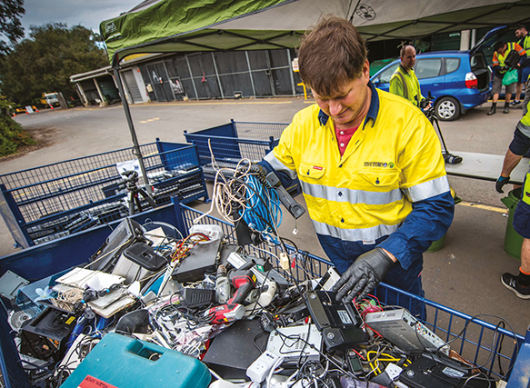 Photograph of a City of Sydney worker sorting e-waste from landfill.