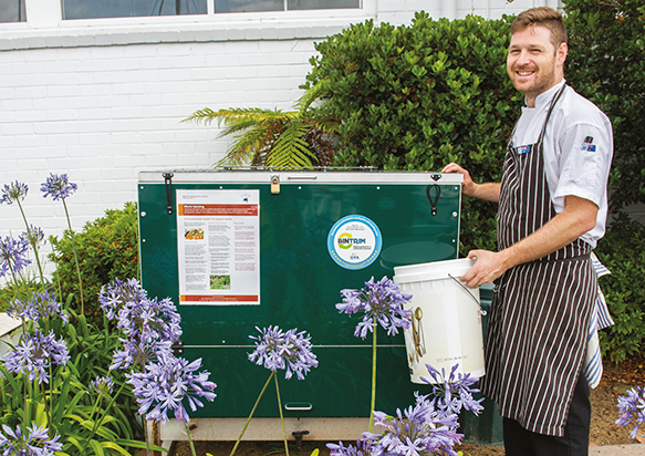 A photograph of a chef attending to a compost system.