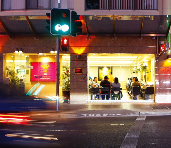 An image of a street in Bankstown at dusk showing people in a busy café in the background.
